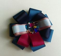 Brooch made ​​of colored ribbons, beads and decorated with stones.