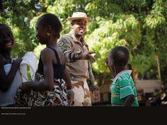 Un militaire joue avec des enfants à proximité du camp. © CCH A. DUMOUTIER