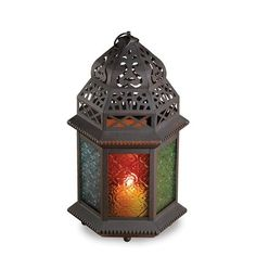The graceful cutouts in this candle lantern's shell throw dancing laceworks of light while patterned glass panels cast a halo of color. Suitable for hanging or use as a free-standing lamp. Rainbow Moroccan Lantern by Rustica House. #myRustica
