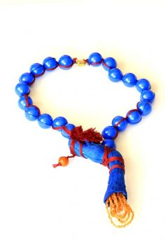 Viktoria Munzker - Necklace - Driftwood, old plastic beads, wine red cotton thread, brass, glass beads, royal blue ink    2012