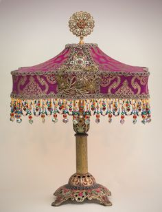Ornate antique brass and metal table lamp has been hand painted and holds a hand-dyed Byzantine Jewel silk lampshade. The shade is covered with beautiful fuchsia and gold metallic antique silk from India.