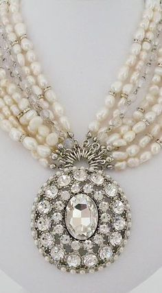 "Badgley Mischka Oversized crystal pendant edged with round pearls is joined by statement strands of freshwater pearls crystals. Pendant is 2 1/4"". Strands consist of 6 freshwater pearls strands with accents of crystal rondelles two linked chains of clear crystals. Shortest strand is 16"" with a 3"" extender."