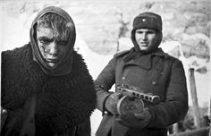 In February of 1943, a Soviet soldier stands guard behind a captured German soldier.