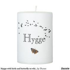 Hygge with birds and butterfly on white pillar candle