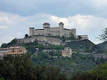 Spoleto (Latin Spoletium) is an ancient city in the Italian province of Perugia in east central Umbria on a foothill of the Apennines. It is 20 km (12 mi) S. of Trevi, 29 km (18 mi) N. of Terni, 63 km (39 mi) SE of Perugia; 212 km (132 mi) SE of Florence; and 126 km (78 mi) N of Rome.