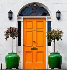 A Lively Orange door with green potted azaleas compliment the entrance.