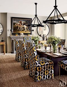 The dining room's chairs are slipcovered in a Dedar print, the light fixtures are by Philippe Anthonioz, and the abaca rug is from Holland & Sherry.