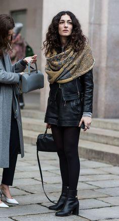 Street style look com shorts preto, jaqueta de couro, meia calça, bota cano curto e maxi scarf no ombro