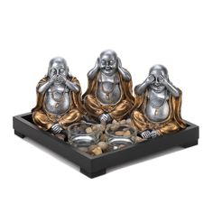 "Invite peace and serenity into your home and remind everyone to speak no evil, hear no evil, and see no evil. The wooden frame of this serenity garden is filled with polished stones, two clear glass candle cups, and three charming Buddha statues.  Set: 8¾"" x 8 5/8"" x 5¼"" high; board is 1¼"" high; each Buddha is 3½"" x 2½"" x 4¼"" high; each candle holder is 2"" diameter x 1"" high.  MDF wood, resin, stones and glass."