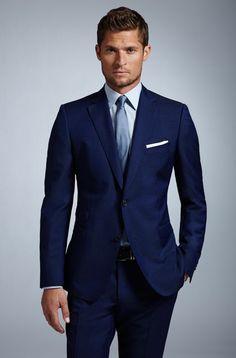 White Pocket Square  — Navy Blazer  — Light Blue Dress Shirt  — Blue Silk Tie  — Navy Dress Pants