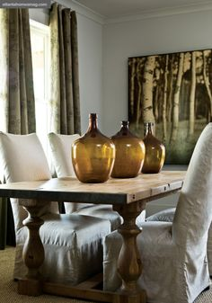Simple country dining room with a wooden trestle table and slipcovered chairs