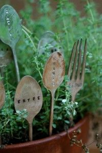 Old silverware plant marker. Sand spoon with steel wool or sandpaper. Wrap in dishcloth and pound back until flat with hammer. Use permanent marker to layout letters. Use metal letter stamping set. Using steel wool or sandpaper, gradually buff away the black permanent marker marks surrounding the letters.
