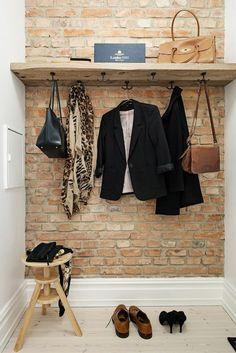 recibidores pequeños, recibidor con pared de ladrillo visto, percha con ropa y bolsas, silla pequeña de madera, decoración moderna