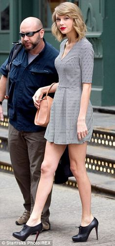 Smart and styled: Taylor teamed the dress with a black jacket, laced black shoe booties and one of her collection of vintage-looking designer bags