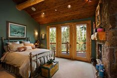 Master bedroom is surrounded by white cedar paneling and log purlins on the ceiling and the natural stone of the fireplace.
