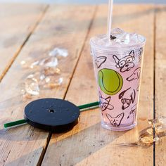 An acrylic Cold Cup tumbler featuring dogs drawn around a bouncing ball.