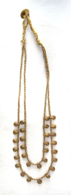 Cute brass necklace with handmade spirals beads hanging.