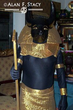 Anubis costume, 2005 for an Egyptian Society party. I stood by the door and some people thought I was a statue until I moved! Mask sculpted, ,molded and cast in urethane resin. Body suit of Spandex, headdress, kilt. pectoral collar, armbands of go;d tissue lame. Was sceptre metal with sculpted head.