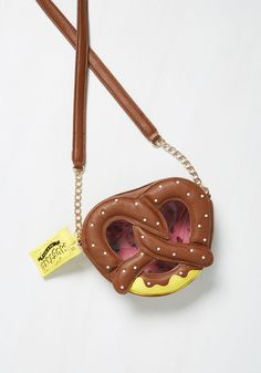 Baby Come Snack Bag. From the moment you slip this pretzel-shaped bag over your shoulder, you wont be able to stop flaunting it! #brown #modcloth