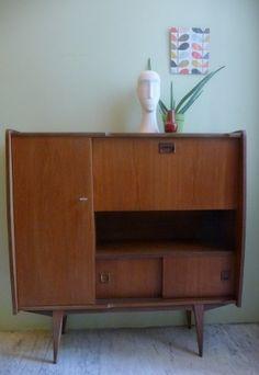 Mid century teak wall cabinet.  Jaren '60 teak wandkast met leuke karakteristieke rondingen. Mooie compacte maat voor in een kleine ruimte. Aan de binnenkant van de klep zit een klein rood vlekje (van inkt?). Verder geen noemenswaardige beschadigingen.  In perfecte vintage conditie.  Afmetingen: h 111 x b 107 x d 34 cm.  Prijs: VERKOCHT SOLD