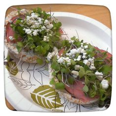 two Lundberg brown rice lightly salted rice cakes topped with black forest smoked ham, organic micro kale, goat cheese,