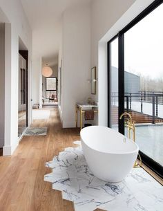 Contemporary bathroom features a white oak floor leading to a marble tiled section of floor accented with an oval freestanding bathtub paired with a brass gooseneck tub filler placed in front of a floor to ceiling window flanked by marble and brass washstands.