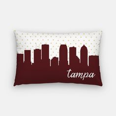 Tampa lumbar pillow featuring a gold polka dot design and the Tampa skyline in your choice of 5 colors:  —Mustard —Navy —Oxblood —Pink —Teal  **Back of pillow will be the solid color you choose (Mustard, Navy, Oxblood, Pink or Teal)  Also, the city name can be included or left off. Please make your choice in the drop down menu  ________________________________________________________ GIMME ALL THE DETAILS:  —Indoor/outdoor pillow measures 12x20 —The insert is hypoallergenic  —Outer case...