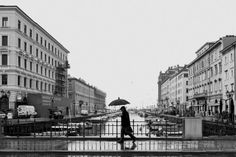 Lonely man walking down a street with his umbrella in rainy weather by Pavel Gospodinov