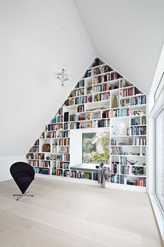 Huge bookshelf is covering a whole wall in this smarthome. The rest of the house is also in this new nordic style.