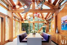 pDouglasfir beams frame the dining room. Fish lamps laminated plywood table and leather benches by Frank Gehry at far...