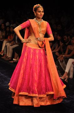 Pink net lehenga with an orange and pink brocade blouse and orange dupatta.