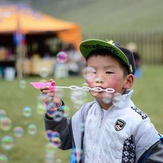 Bulles de savon et festivités en #Mongolie. Bubbles of fun in #Mongolia. #kid #fun #green #fly #cap #cutekids #igs_asia @everydayasia