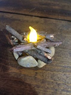 Flickering Fire Pit Miniature perfect for your fairy garden, gnome garden, or miniature garden! The fire pit features rocks around the perimeter and real wood by the faux 'flame'. The fire pits flicke