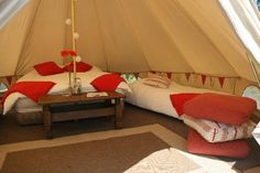 I like the brightness of the red pillows - and a table with flowers makes glamping divine!