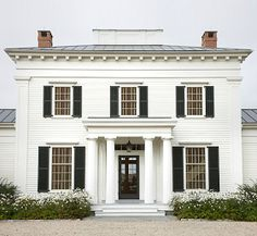 A new Greek Revival home by GP Schafer. Doric columns, twin chimneys, and black shutters. Black Shutters, Exterior Shutters, Louvered Shutters, White Siding, Country Shutters, Exterior Paint, American Houses, White Houses, Home Fashion