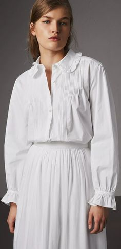 A feminine shirt by Burberry in light Italian-woven cotton. Textured with a finely pintucked front and subtle embroidery, the design features ruffles at the collar and cuffs. Gathering at the sleeve and back add volume.