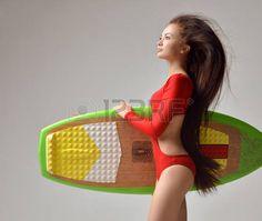 teen girl bikini: Hermosa morena mujer joven con el pelo largo en bikini rojo y tabla de surf sobre un fondo gris Foto de archivo