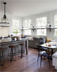 modern farmhouse kitchen - In the kitchen, the cabinets are Shaker, the metal fixtures are industrial or barn style such as gooseneck. Wood is always present and in mixed tones.