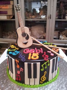 Wicked Chocolate cake iced in chocolate ganache, decorated with fondant piano keys, 3D edible acoustic guitar, 3D edible drum sticks & piped musical notes