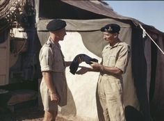 GENERAL BERNARD MONTGOMERY, COMMANDER OF THE EIGHTH ARMY, ITALY, 30 SEPTEMBER 1943. General Montgomery is handed a scarf by his batman, Corporal W English, in camp at Eighth Army Headquarters in Italy. Corporal English, from Erith, has been the General's batman since Alamein.