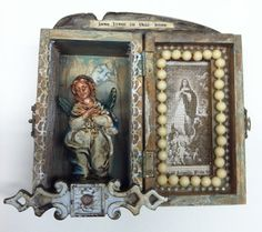"""This assemblage altar is created inside of a wooden box . The box is permanently propped open. The main figure is a vintage chalk nativity Mary that has been given new handmade ceramic wings. The other side of the box features a vintage prayer card peeking through old screen.  A piece of vintage hardware, lace, and a broken chair part completely the piece. The words """"love lives in this home"""" grace the top of the altar."""