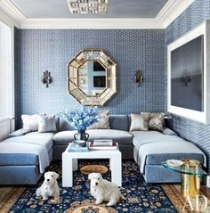 The homeowners' Sealyham terriers gather in a family room of the same apartment, where the walls—sheathed in a John Robshaw fabric—display an Italian mirror and a Hiroshi Sugimoto photograph; the ceiling fixture is by Mathieu Lustrerie, and the sectional sofa, in a Jasper silk mohair, is by Jonas | archdigest.com