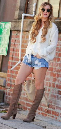 Casual fall outfit styled with a chunky lace up sweater, distressed jean shorts, GiGi New Yor bucket bag, and tall suede boots