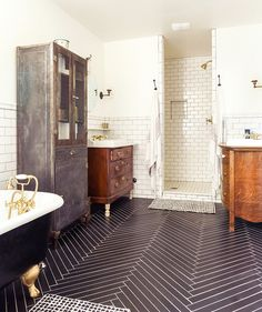 A cool bathroom with herringbone tile on the floor, a footed tub, tall metal cabinet, and multiple sinks