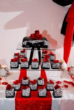 torre con torta y Mini tortas con detalles en negro y decorados con petalos de rosas rojas muy romantico!!