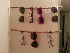 9 strings of twine, braided in threes and strung taut on L-hooks. Simple DIY sunglasses storage solution.