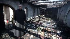 A priest inspects damage caused to the Church of the Multiplication of the Loaves and Fishes in Galilee, Israel, by an arson attack (18 June 2015)