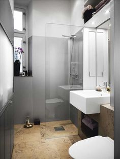 The eye follows the continuous floor past the invisible glass shower wall..small bathroom, great illusion of space