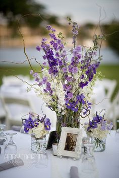 Purple Lavender and White Centerpiece: Mason jars of white hydrangea, purple iris, lavender sweet peas and dried lavender are reused on the reception tables to accent the stunning taller centerpiece of white, lavender, and purple larkspur by Andrea Layne Floral Design (www.andrealaynefloraldesign.com)