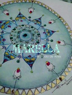 Mandala em aquarela com tons de verde náutico, dourado e vermelho. Diâmetro médio de 25cm. Moldura padrão branca.
